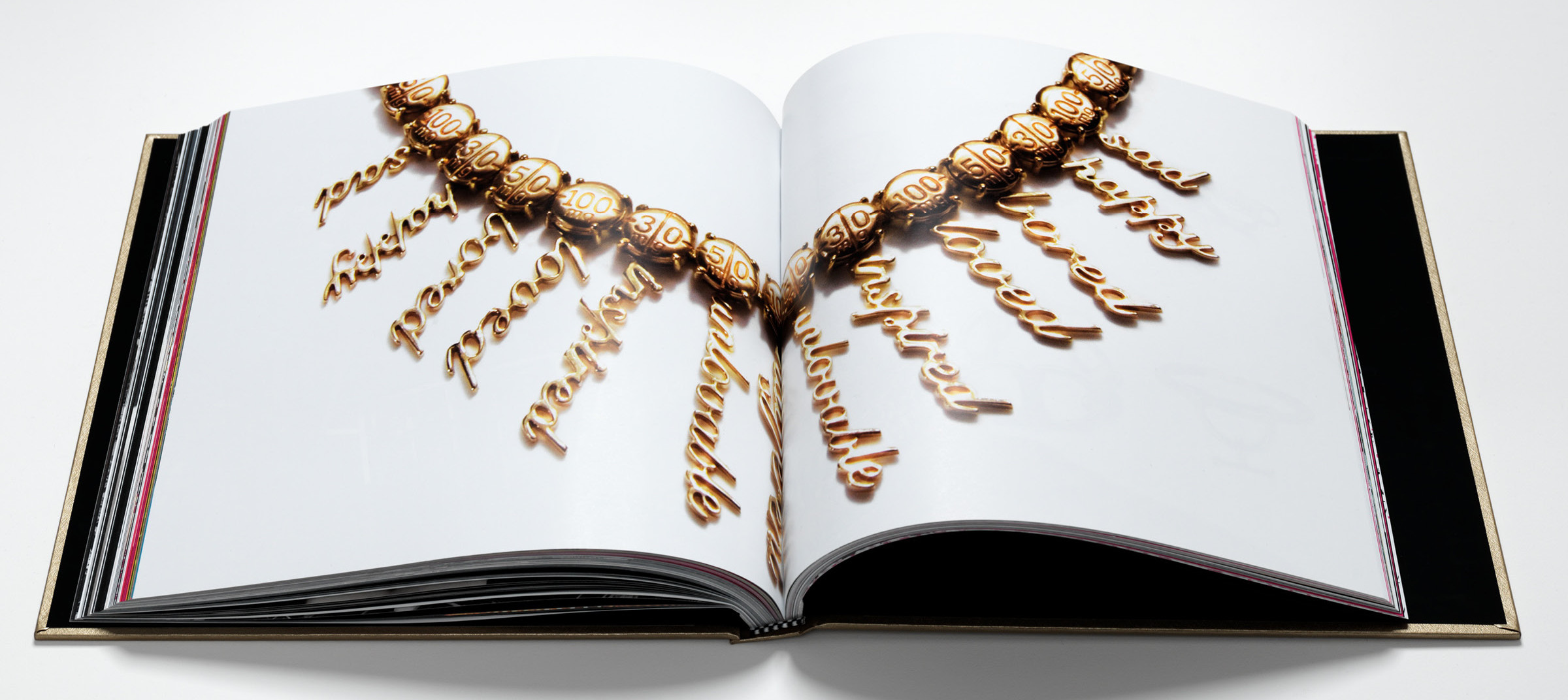 Spread showing gold necklace in a DTE created custom designed brand book for luxury jewelry brand Fenton Fallon