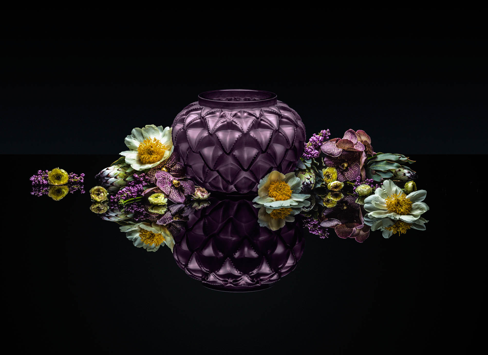 Wide purple Lalique vase surrounded by flowers