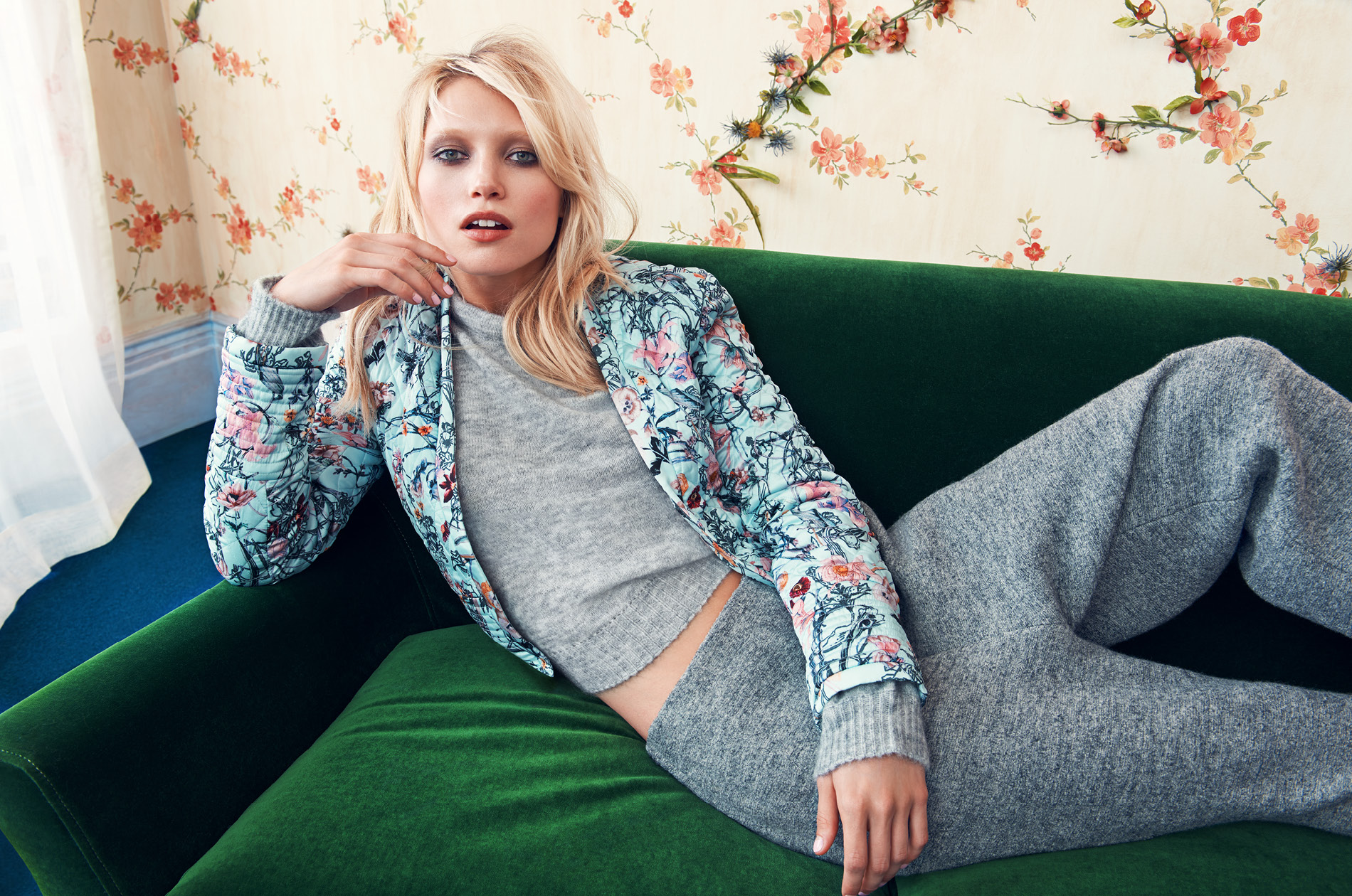 Model posing for a fashion campaign, wearing a floral coat.